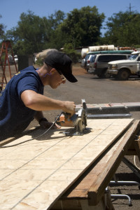 Builder 2nd Class Christopher Farmer cutting soffit boards